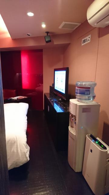 HOTEL THE SCENE(ザ・シーン)(横浜市港北区/ラブホテル)の写真『502号室 トイレの方に曲がらず部屋に向かった景色。右手前から空気清浄機、ウォーターサーバー、テレビ、上にエアコン。左にベッドが見える』by なめろう